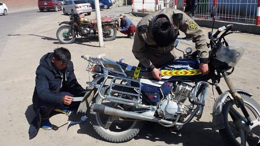 Мотоциклийн үзэгдэх орчныг сайжруулахаар гэрэл ойлгох туузыг нааж байна